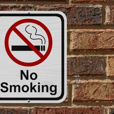No Smoking Sign, Red and White sign with words No Smoking and cigarette symbol on a brick wall
